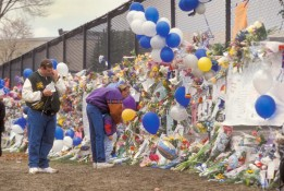 A father comforts his daughter as they look at tributes left on a Clement Park fence as another visitor weeps.
